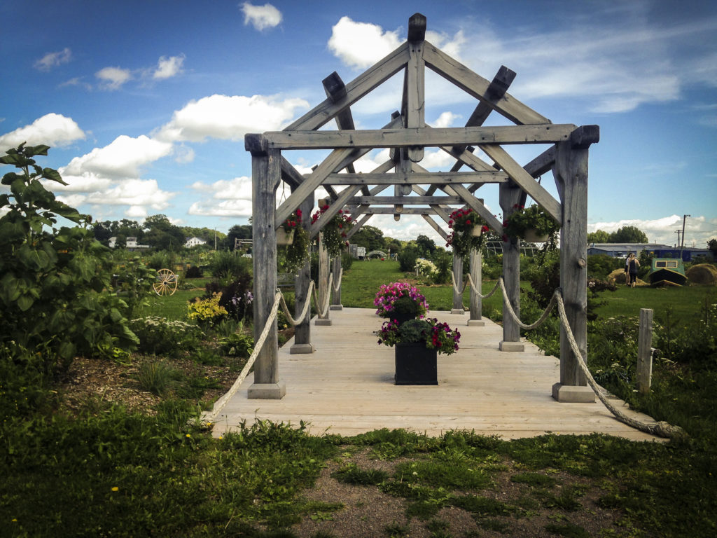 Entrance to Legacy Garden, wooden boardwalk with wooden frame.