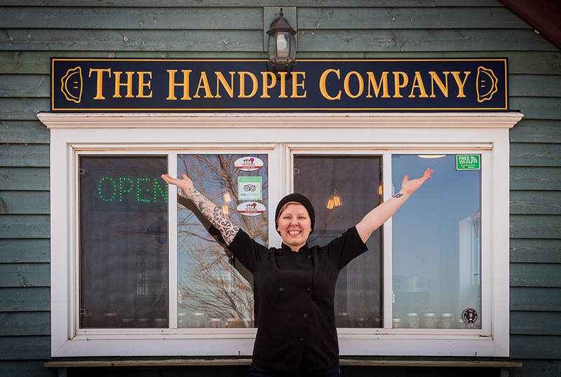 Chef Sarah Bennetto O'Brien shows off the sign for her new business, The Handpie Company
