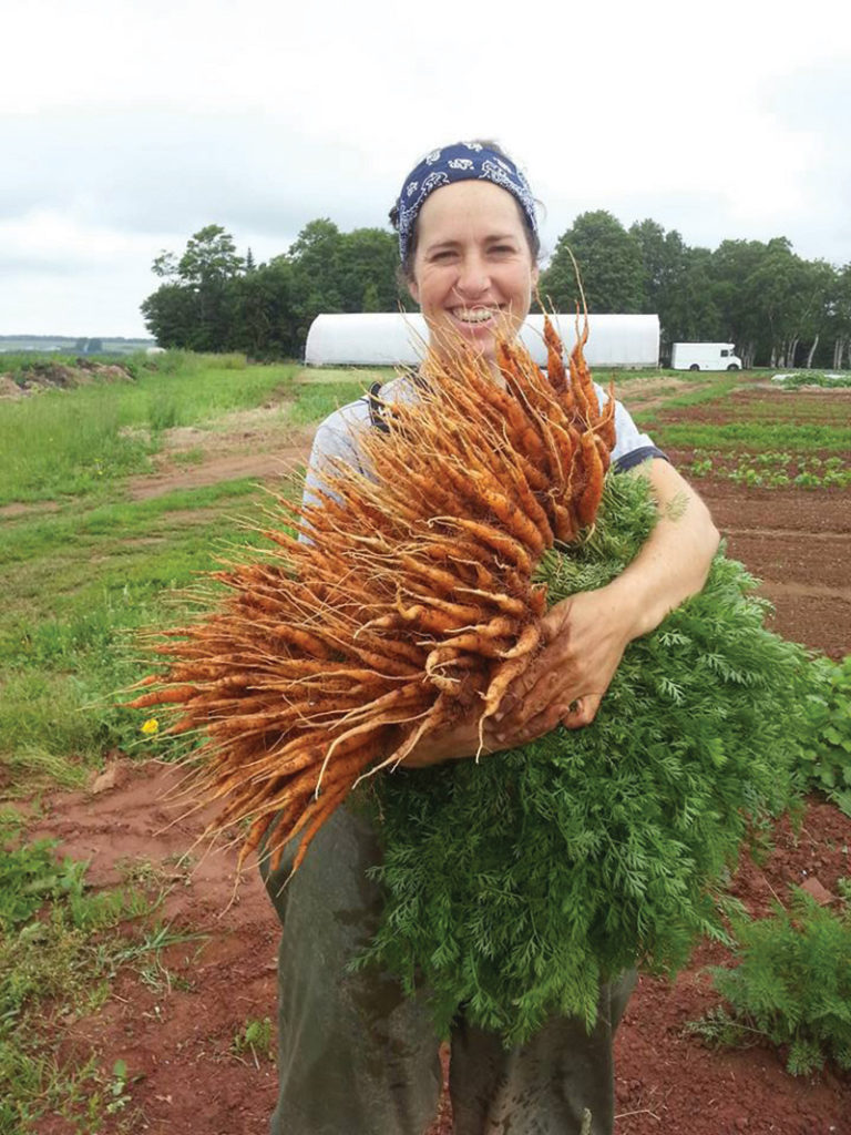 Jen Campbell holding a big bunch of freshly harvested carrots
