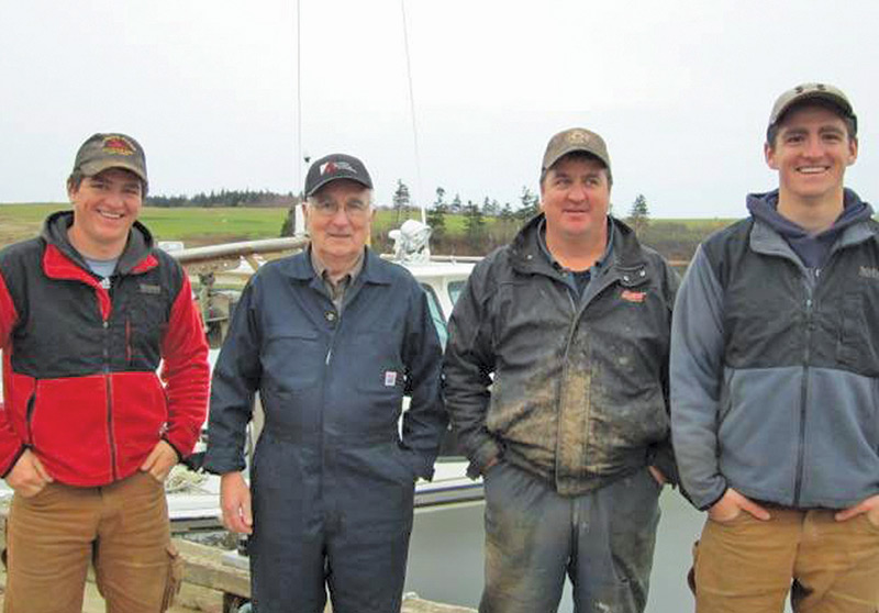 Four lobster fishermen representing three generations of the Blacketts pose in front of a fishing boat.