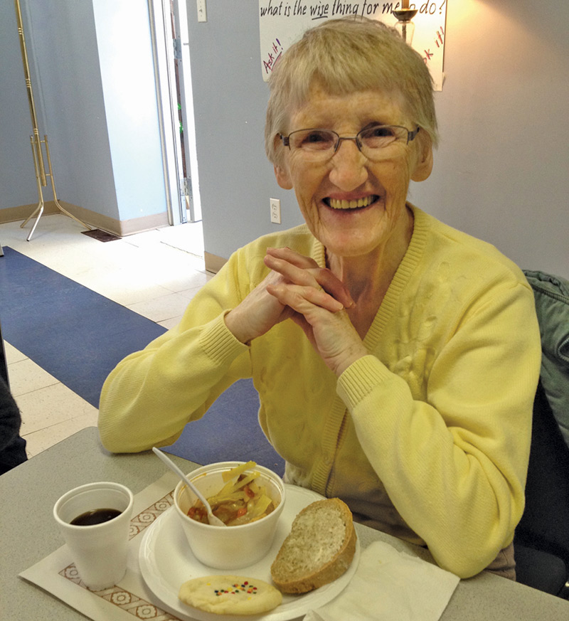 Elderly woman enjoying a bowl of soup and some bread at Soul Soup