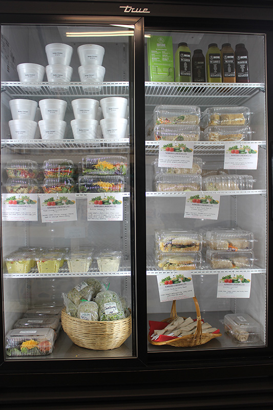 Cooler with glass doors stocked with prepared soups, salads and other dishes.