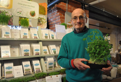 Allan Bridle hols sprouting kit in front of his booth at Summerside Farmers Market