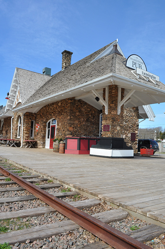Exterior shot of Island Stone Pub, with railway tracks in foreground. Building made of fieldstones.