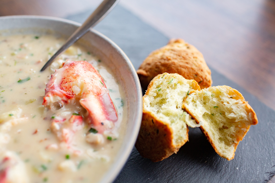 bowl of lobster chowder with cheddar cheese scones