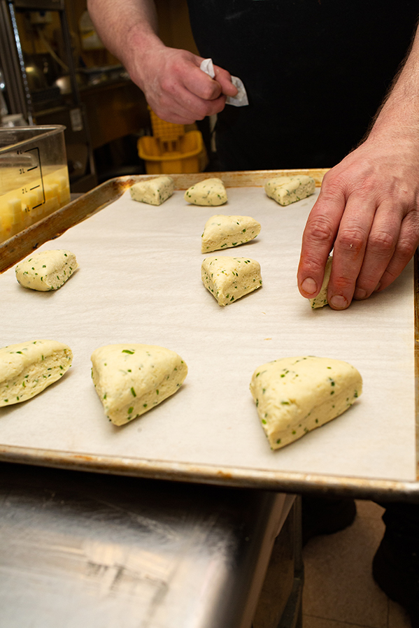 Wedges of dough are placed on the parchment-lined cookie sheet to go into the oven.
