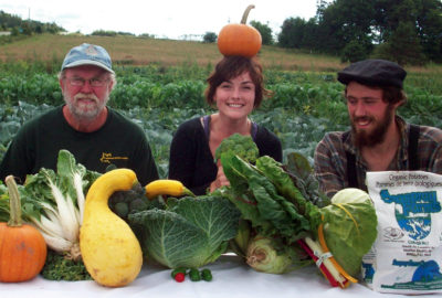 Reg Phelan, Carina Phillips and Byron Petrie showcase a table filled with vegetables grown on their farm, Seaspray Organics