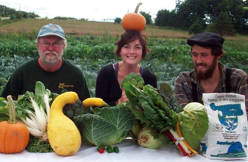 Reg Phelan, Carina Phillips and Byron Petrie showcase a table filled with vegetables grown on their farm, Seaspray Organics