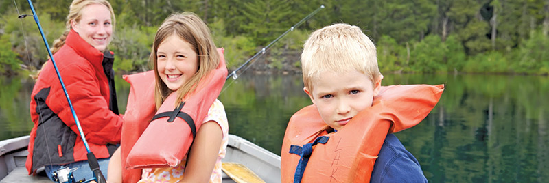 Two children and an adult with life jackets on in a boat fishing.